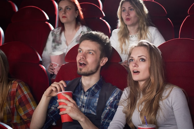 열린 된 입으로 영화관에서 화면을보고 충격 된 부부의보기. 무서운 영화를 즐기는 회색과 잘 생긴 남자에 예쁜 금발 소녀. 친구와 자유 시간의 개념.