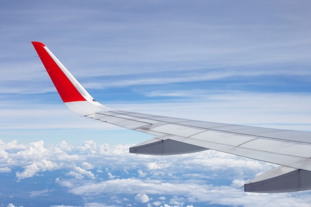 窓からの空の雲と飛行機の翼の眺め
