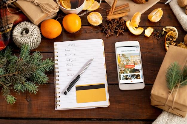 Вид на смартфон с промо, блокнот с ручкой, список и кредитную карту в окружении традиционных рождественских вещей на столе
