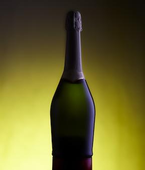 Вид бутылки игристого вина на желтом фоне