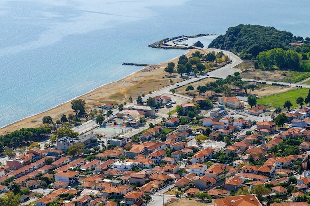 Вид на стратонион с дрона, несколько зданий с красными крышами на берегу эгейского моря, много зелени и игровые площадки, греция