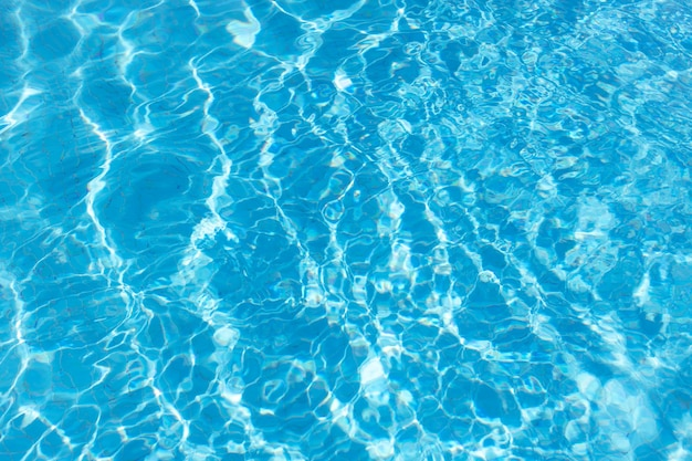 スイミングプール、夏の背景のターコイズブルーの水の表面のビュー。波のある色のグラデーション。