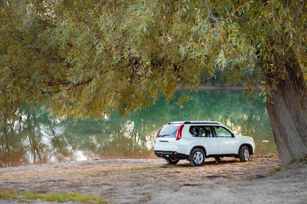 일몰에 강 해변에서 suv 자동차의 보기. 복사 공간