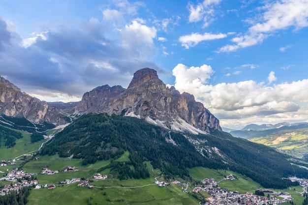 Вид на альпийские деревушки кольфоско и корвара у подножия горы сассонгер