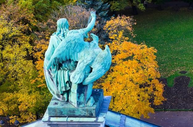 Вид на старинные статуи человека и орла из лепнины и купол исаакиевского собора петербург.