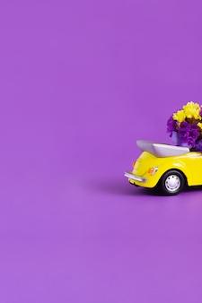 紫色の花の花束と明るい黄色のコンバーチブル車のトランクの背面のビュー。コンセプトホリデー、配達、アート、輸送