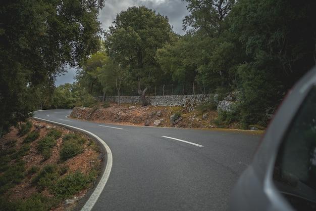 Вид сзади автомобиля, едущего по горной дороге
