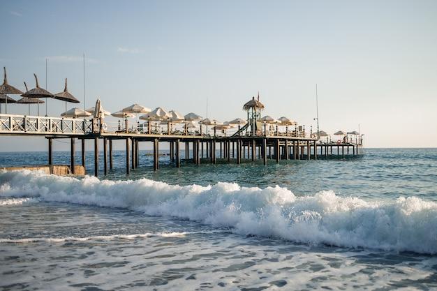 ビーチと地中海の眺め、暖かい晴れた日の美しい澄んだ海の水。暖かい国での休息の概念。水上に立つ木製の桟橋