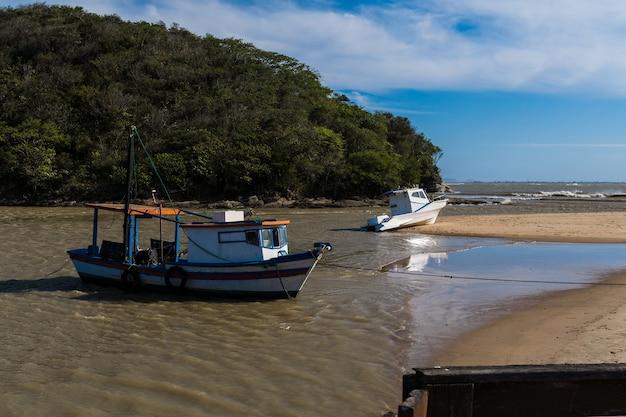 Вид на пляж рио-дас-острас со встречей реки в рио-де-жанейро. солнечный день, голубое небо. желтый песок и несколько камней. деревянный мост для перехода. лодки и рыбалка на пристани.