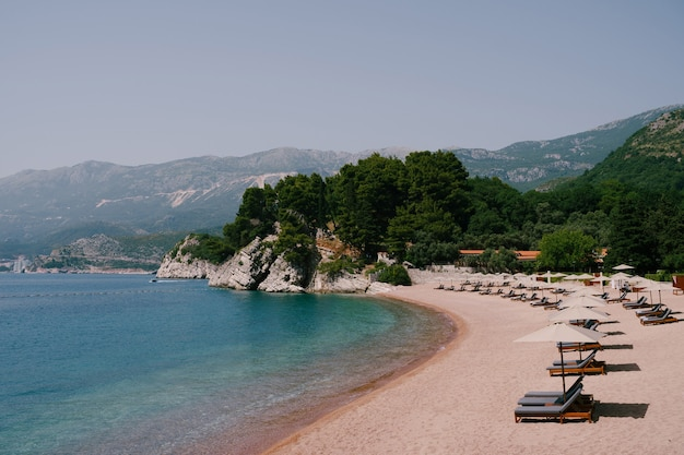 Sveti 근처의 녹색 산을 배경으로 일광욕 의자와 파라솔이있는 해변의 전망