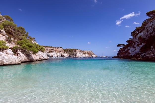 Вид на красивый маленький пляж cala macarelleta с чистой изумрудной водой острова менорка, балеарские острова, испания