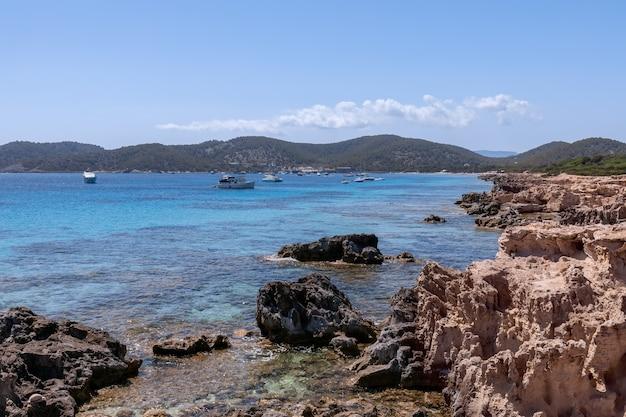 Вид на красивое скалистое побережье, бирюзовое море с лодками на ибице, испания