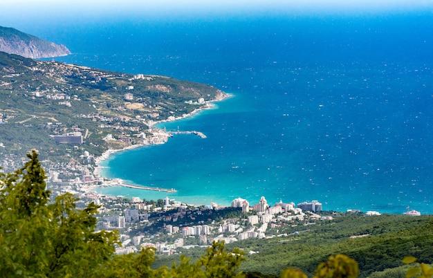 Вид на черное море с горы ай-петри. ниже села алупка большая ялта. пасмурная солнечная погода.