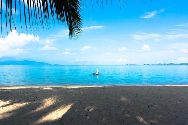 Вид на синее море и рыбацкую лодку под пальмами на пляже. самуи таиланд