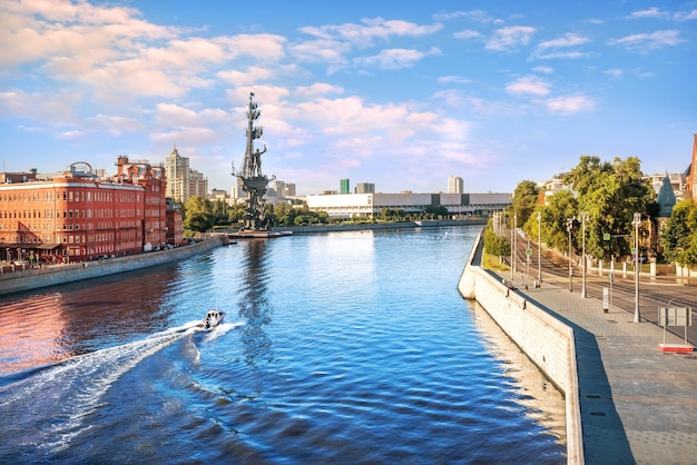 Вид на лодку на москва-реку и памятник петру великому в москве с патриаршего моста на утреннем солнце