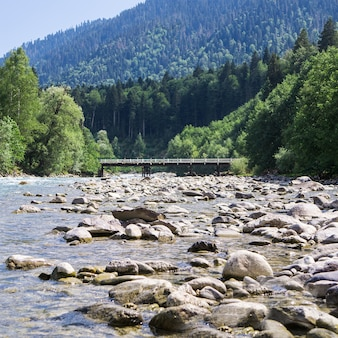 Вид на мост через лазурную реку на фоне красивого горного пейзажа
