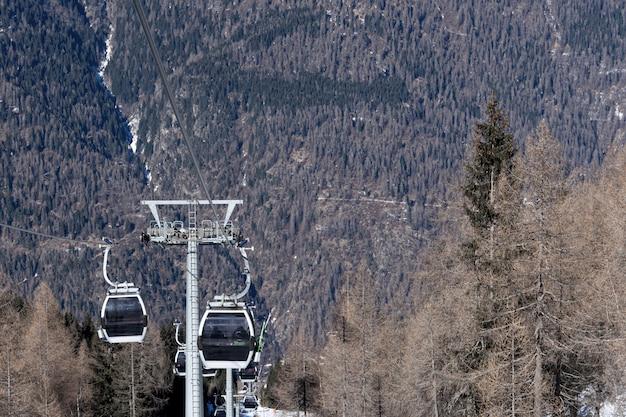 Взгляд канатной дороги с лыжниками гор на наклоне в предыдущую весну. концепция пейзаж, спорт.