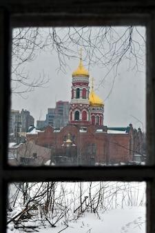 오래 된 집의 창을 통해 교회의 보기