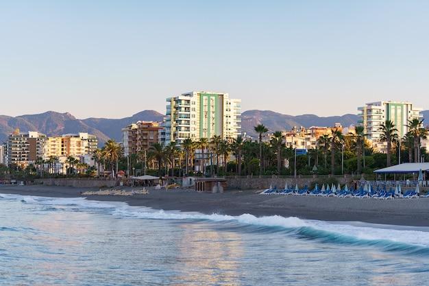 Вид на городские постройки у морской линии лазурной морской воды. пляж. современные дома и отели у моря. турция