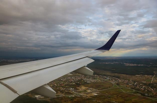 飛行機の窓の青い空、飛行機の翼の明るい雲を飛んでからの街の眺め