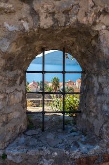 要塞モンテネグロの石垣にある火格子のある穴から、ヘルツェグノビの街、青い海、建物を眺めることができます。美しいボカコトルスカ湾の入り口にある町