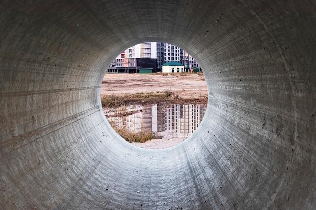 コンクリートパイプを通しての建設現場の眺め。建設中のパイプの取り付け。