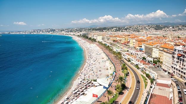 Вид на лазурный берег в ницце, франция многократные отдыхающие на пляже люди, строящие голубую воду