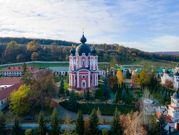 ドローンからのクルキ修道院の眺め。教会、その他の建物、緑の芝生、散歩道。遠くに緑のある丘。モルドバ