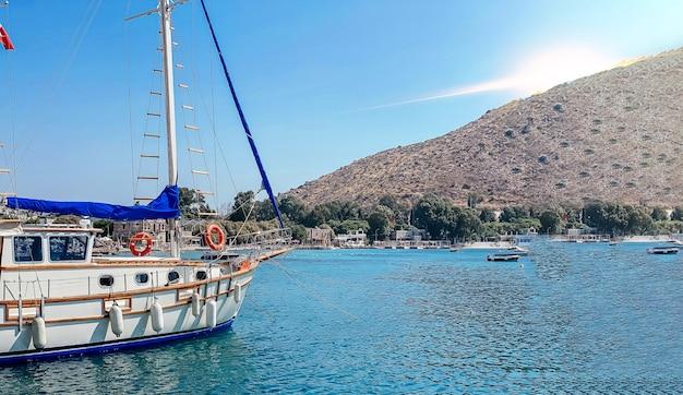 桟橋のヤシの木に係留されたボートとトルコのリゾートタウンの堤防の眺め