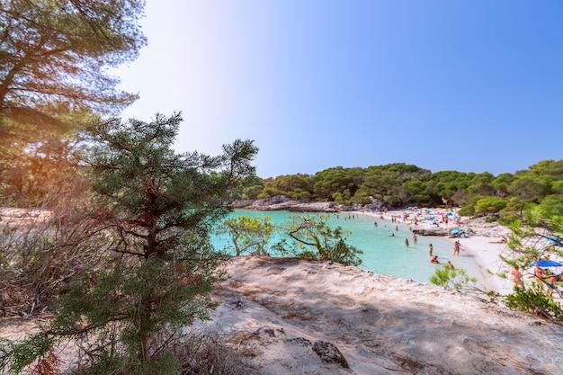 Вид на знаменитый пляж cala turqueta. (сосредоточьтесь на переднем плане, люди на пляже в размытом виде). менорка, балеарские острова, испания