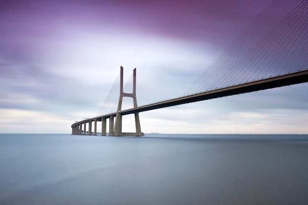 Вид на знаменитый мост васко да гама через реку тежу в лиссабоне, португалия. место для текста.