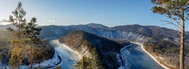Вид на замерзающую реку ману осенью с горы. природа сибири, красивый пейзаж.