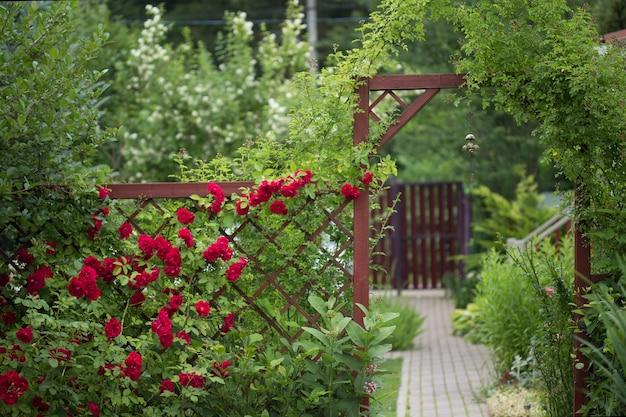 녹지에 싸여있는 빨간 문이있는 정원 풍경과 전경에 매달려있는 중국 종을 볼 수 있습니다.