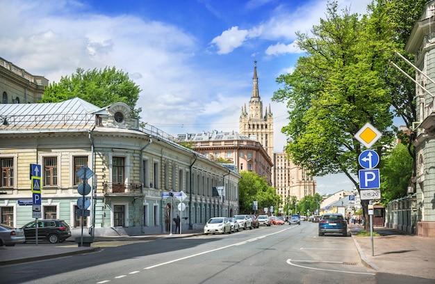 Вид на высотку на кудринской площади с поварской улицы в москве в солнечный летний день. надпись: трубниковский переулок.