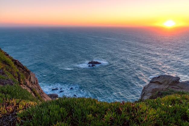 Вид на горизонт и заходящее солнце со скал кабо-да-рока на закате. самая западная точка европы. синтра, португалия.