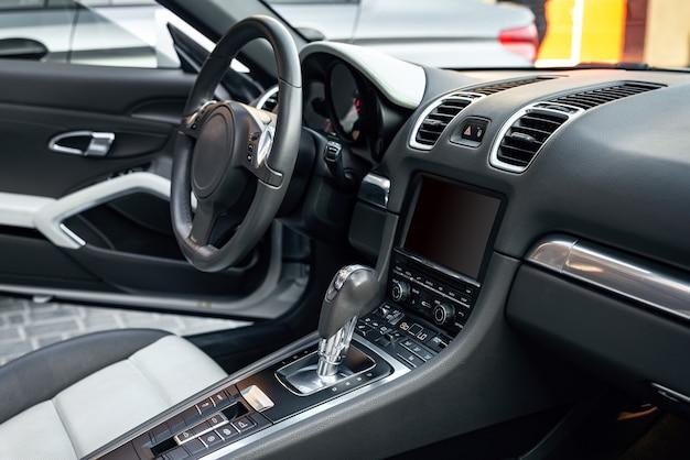 Вид на салон роскошного кабриолета, современная приборная панель с сенсорным экраном, белые кожаные сиденья, идеально подходящие для водителя. выборочный фокус.