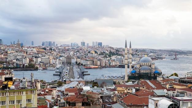 Вид на стамбул в пасмурную погоду, пролив босфор, разделяющий город на две части, несколько зданий, новую мечеть и мост с автомобилями, турция