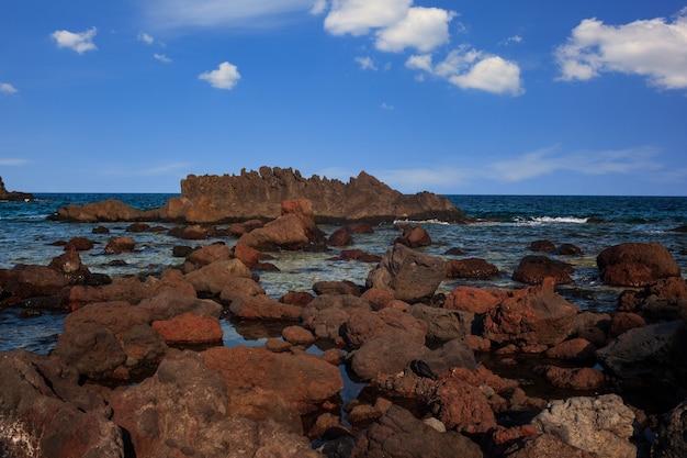 Вид на лавовый пляж линозы, называемый фараглиони, сицилия. италия