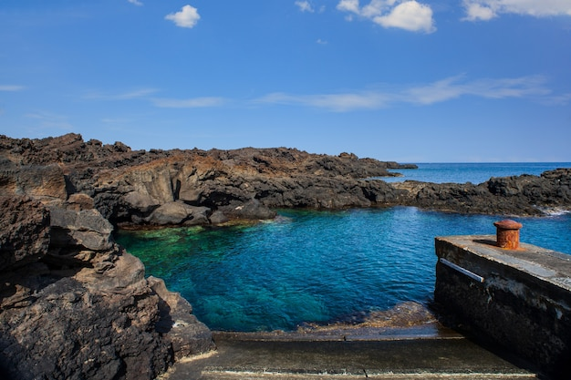 Вид на лавовый пляж линозы под названием маннарацца, сицилия. италия
