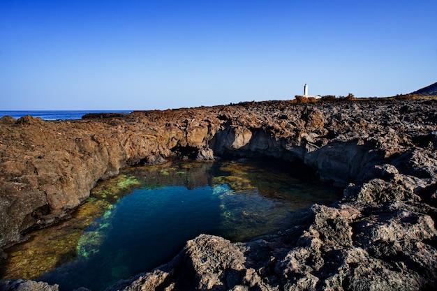 Вид на лавовый пляж линозы, называемый писцином, сицилия. италия