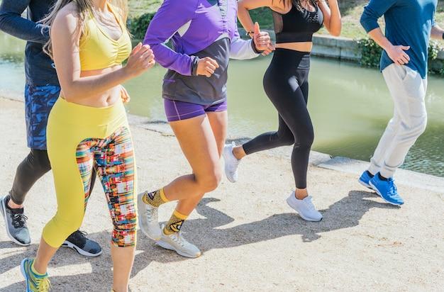 公園でトレーニングしている何人かのランナーの足の眺め。水平フレーミング。