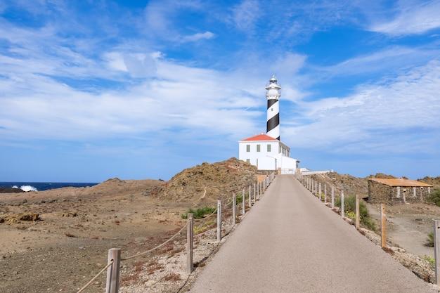 Вид на маяк (faro de favaritx) в солнечную погоду с красивыми облаками в небе на острове менорка, балеарские острова, испания