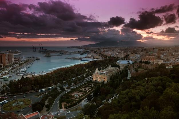 スペイン、マラガ市の眺め。照らされた建物と劇的な夕焼け空のある市庁舎と港の空撮。