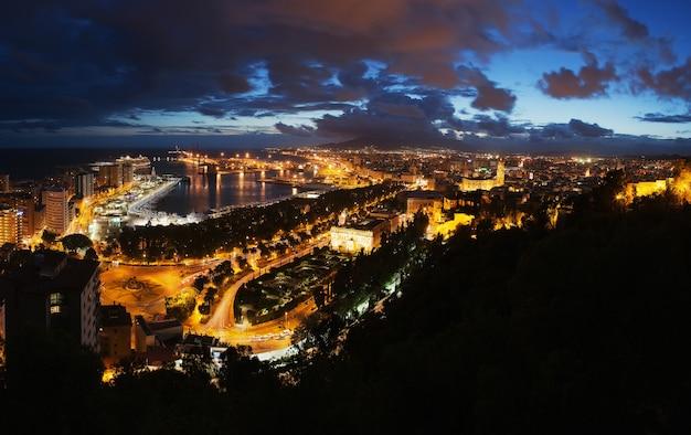 スペイン、マラガ市の眺め。夕焼け空と夜の照らされた建物と市庁舎と港の空撮