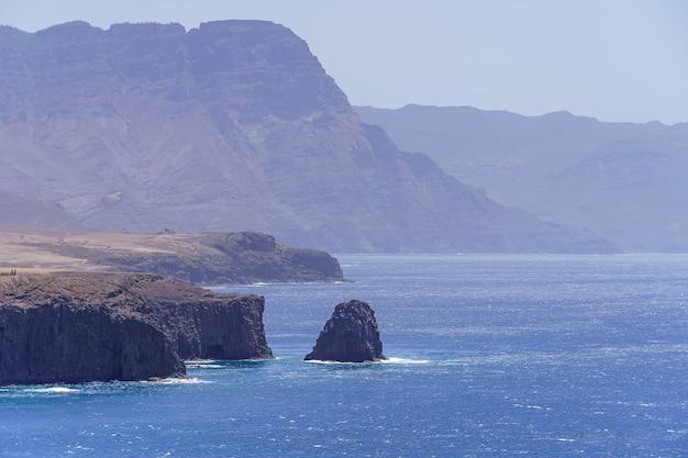 그란 카나리아 스페인의 푸른 물에서 나오는 높은 절벽과 바위가있는 해양 해안선의 전망. 유럽