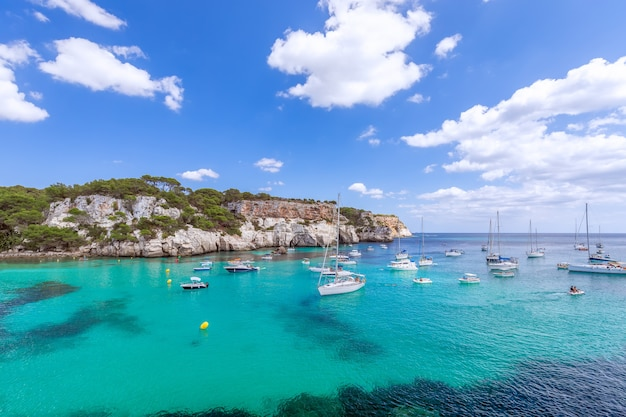 Вид на красивейшую бухту cala macarella острова менорка с изумрудной водой и множеством яхт на море. балеарские острова, испания