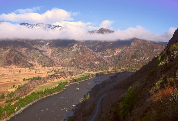 Вид на долину горной реки высокие горы на берегу утопают в бело-розовых облаках.