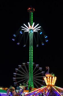 Вид на ночной парк развлечений. колесо обозрения, яркие карусели.