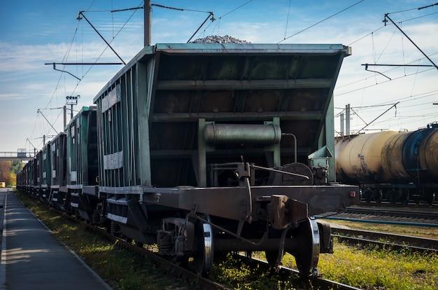 Вид старой пыльной железной дороги с грузовыми вагонами и линиями электропередач