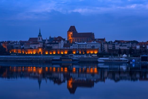 夜明けにイルミネーションとトルンの古いポーランドの町のビュー